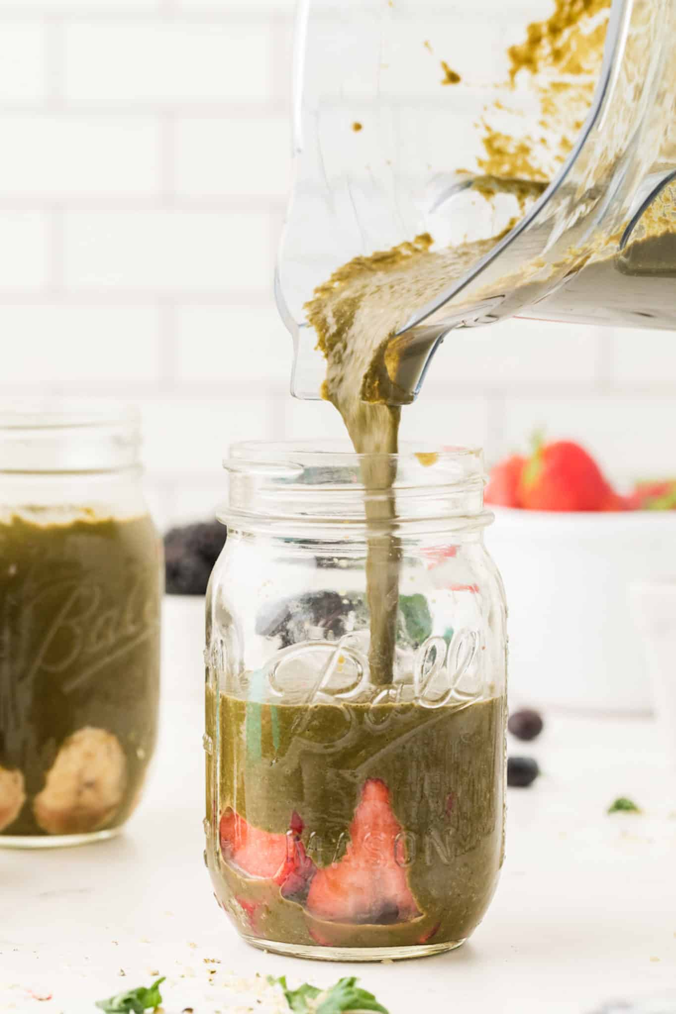 photo showing pouring a green smoothie into a jar