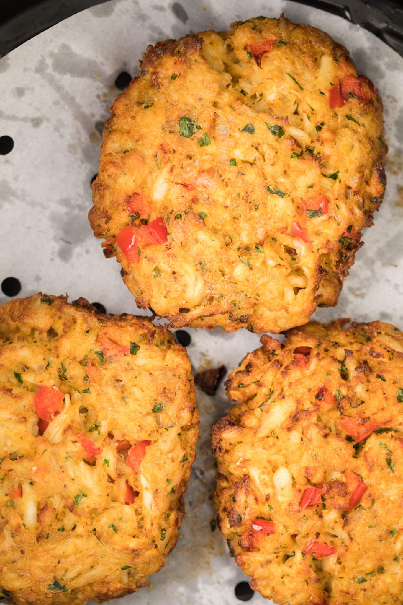 baked crab cakes on parchment paper liner in air fryer basket