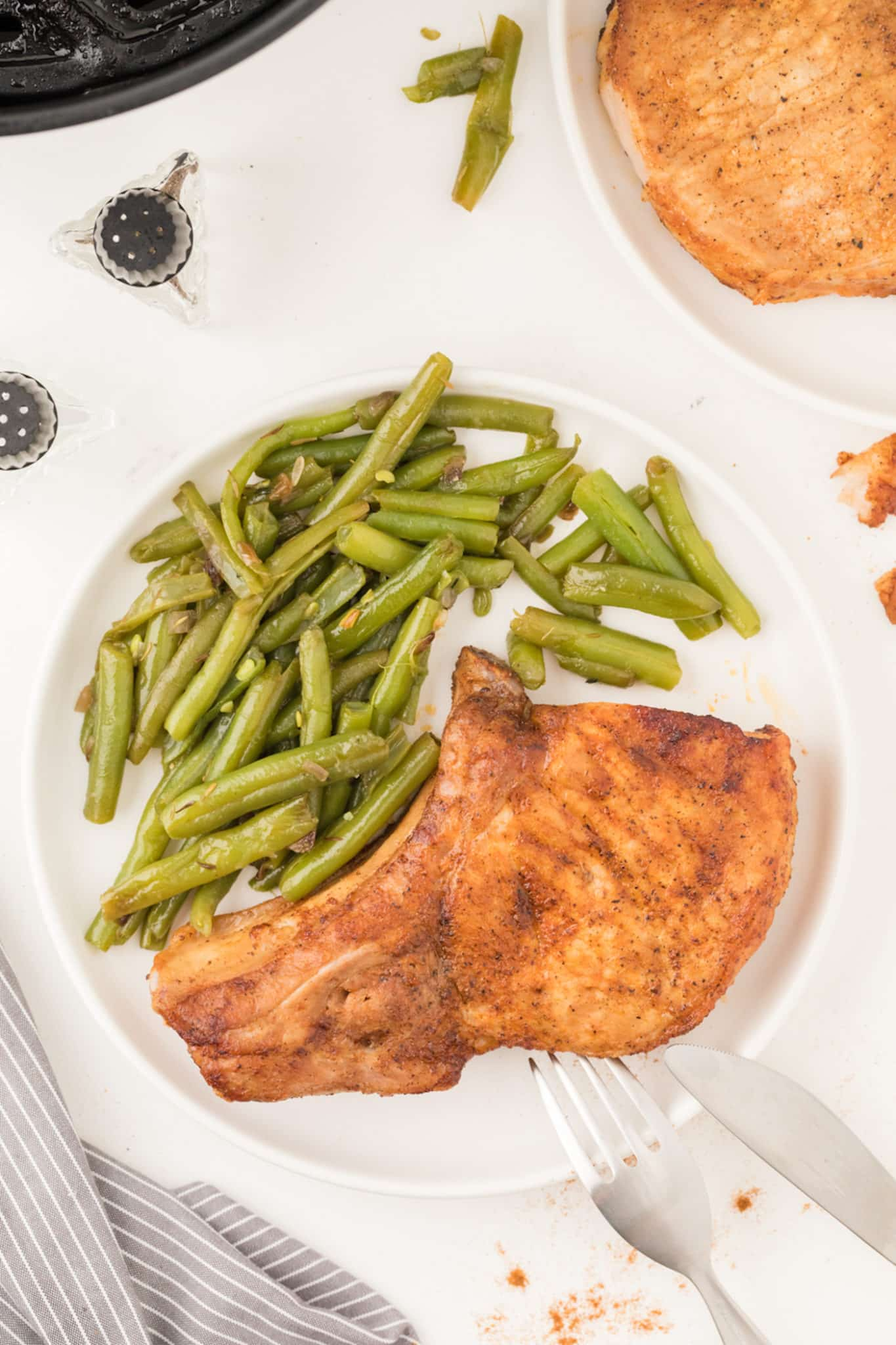 pork chops served on a plate with green beans