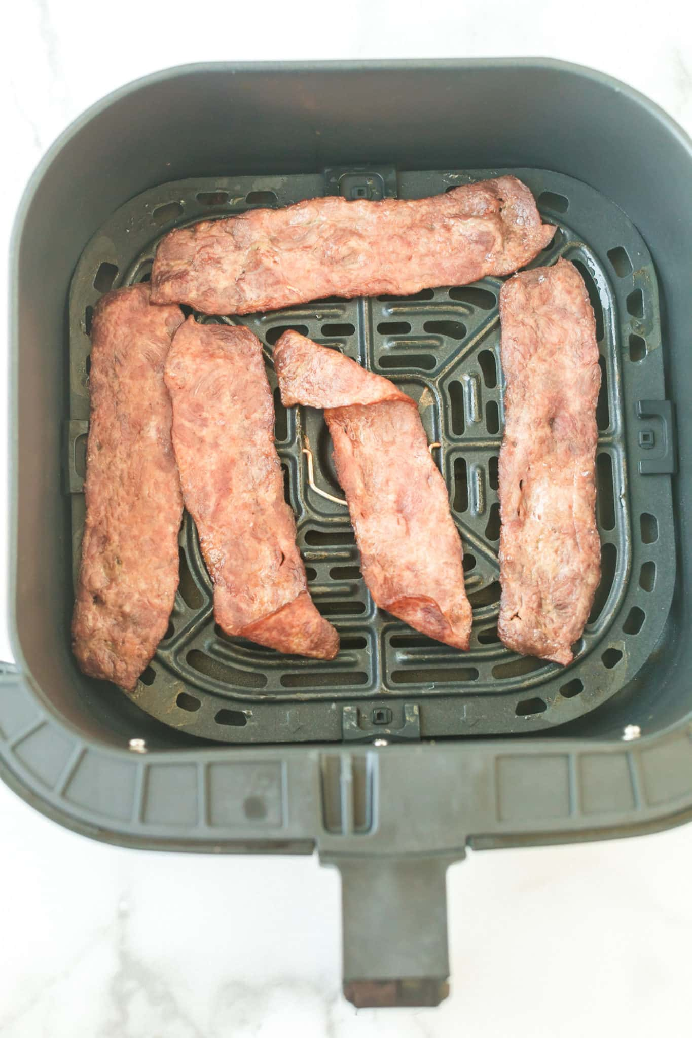 five slices of cooked turkey bacon in an air fryer