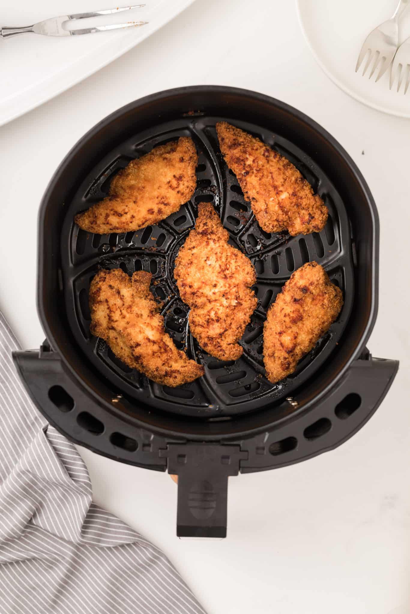 cooked breaded chicken tenders inside air fryer basket