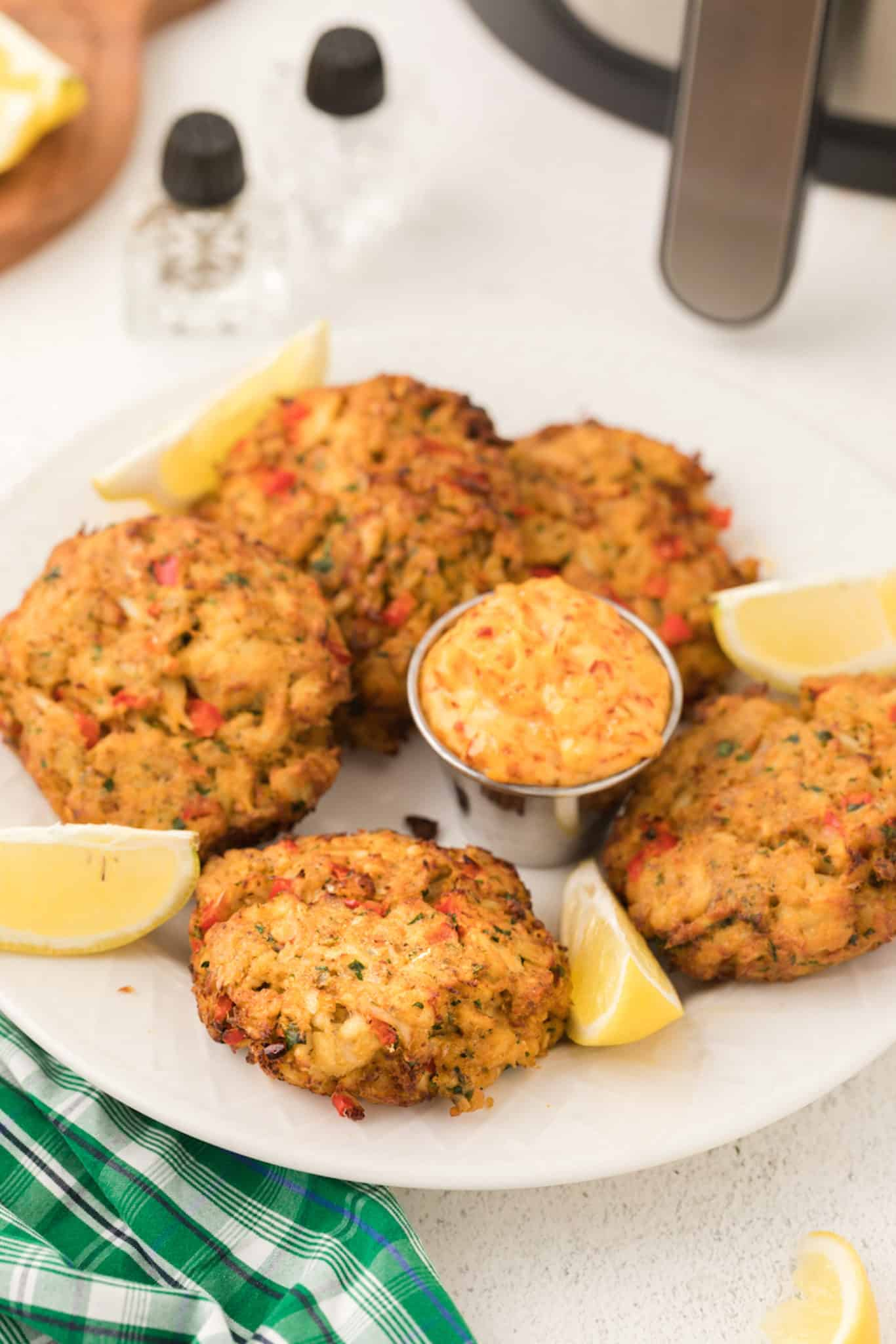 serving plate with crab cakes, lemon slices, and dipping sauce