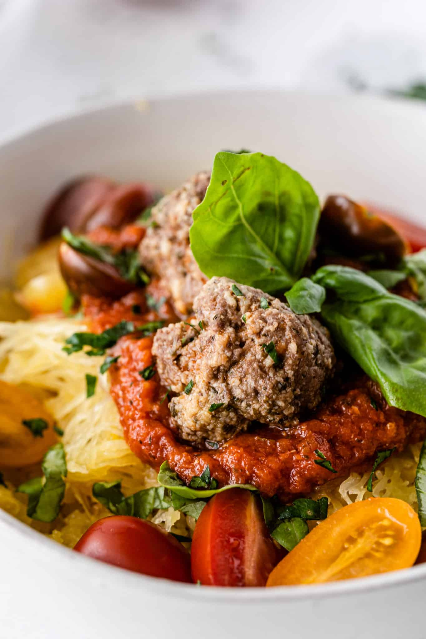 meatballs served in a bowl with spaghetti squash and marinara