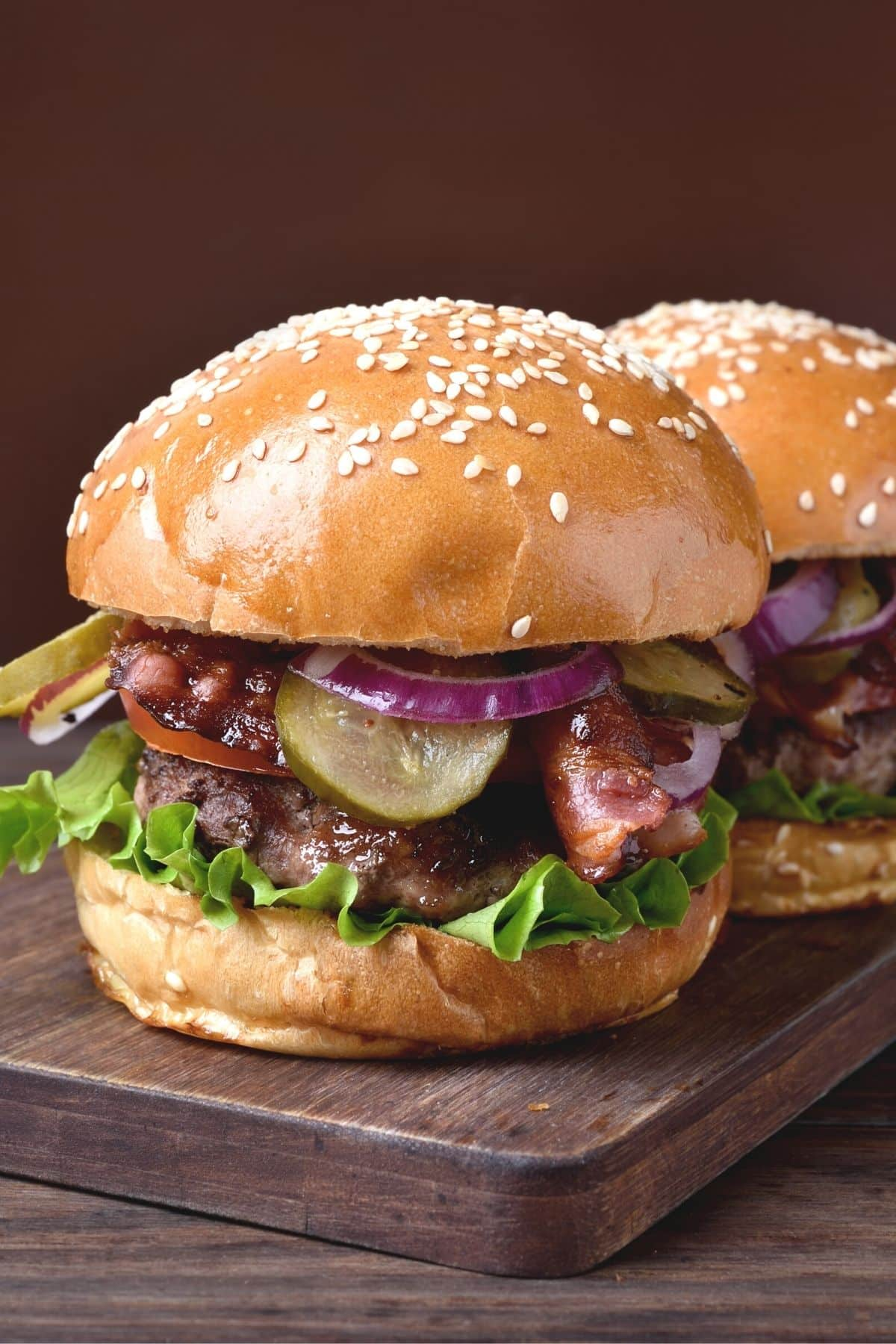two hamburgers on buns ready to eat