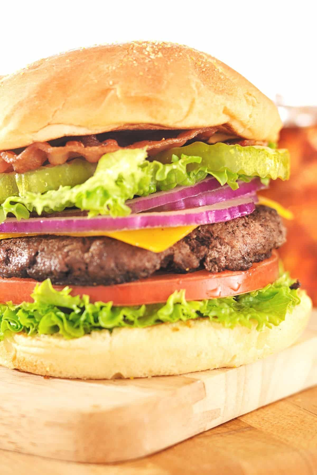 hamburger served with bacon, pickles, lettuce, cheese, onion, and tomato