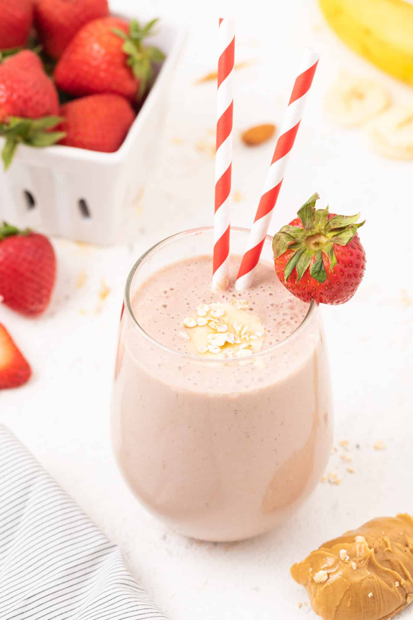 oat milk smoothie served in a glass with a red striped straw