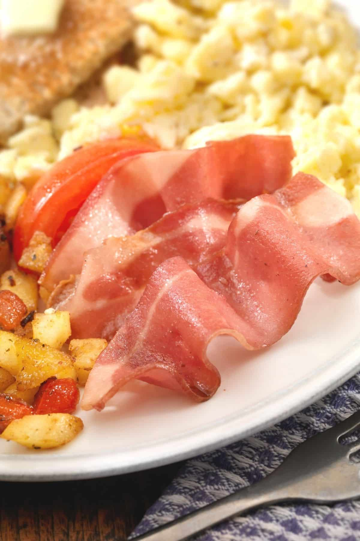 turkey bacon served on a plate with scrambled eggs and potatoes