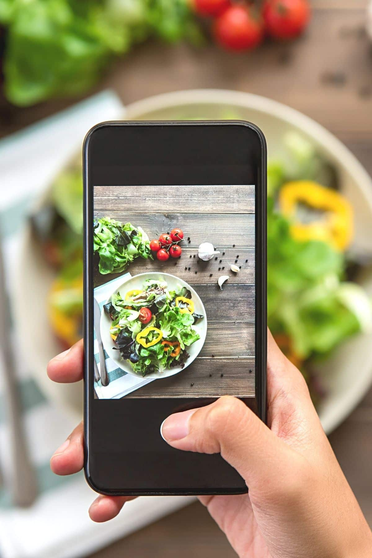 A person taking a picture of a salad with a phone