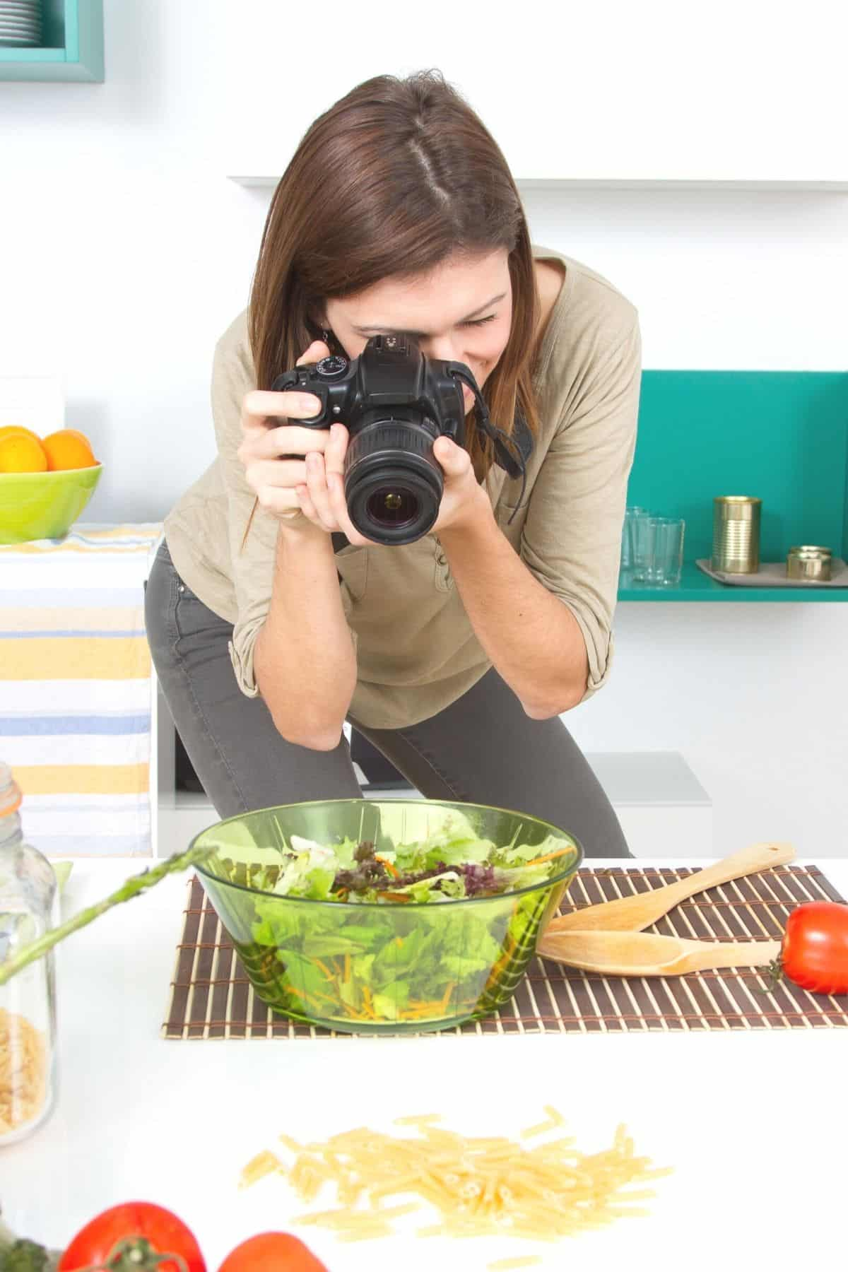 woman taking picture of a salad