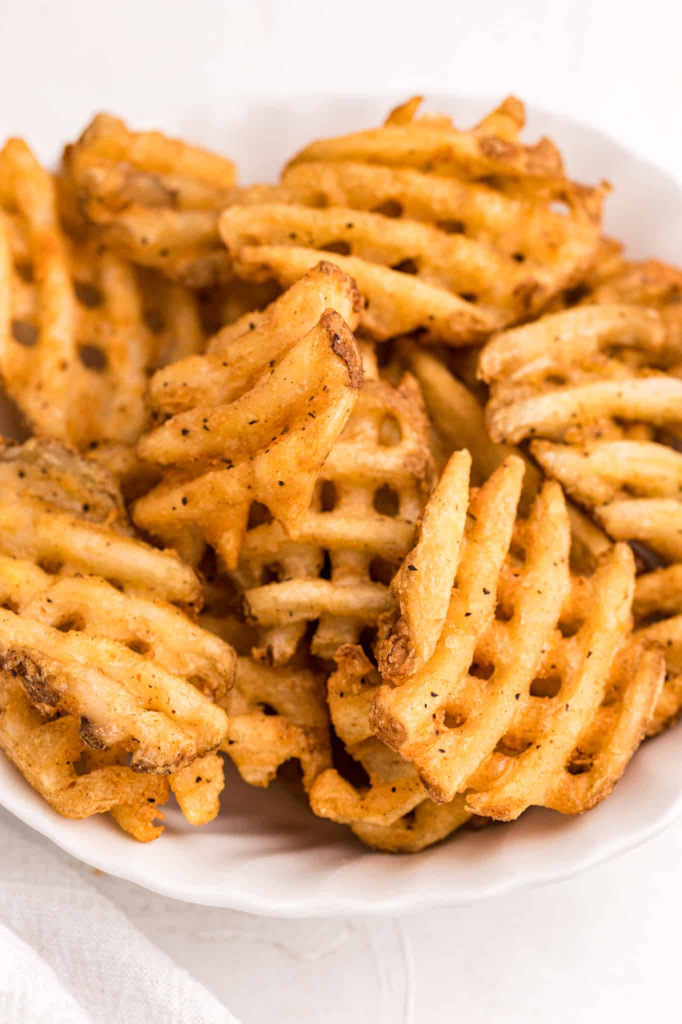 crispy waffle fries served in a white bowl
