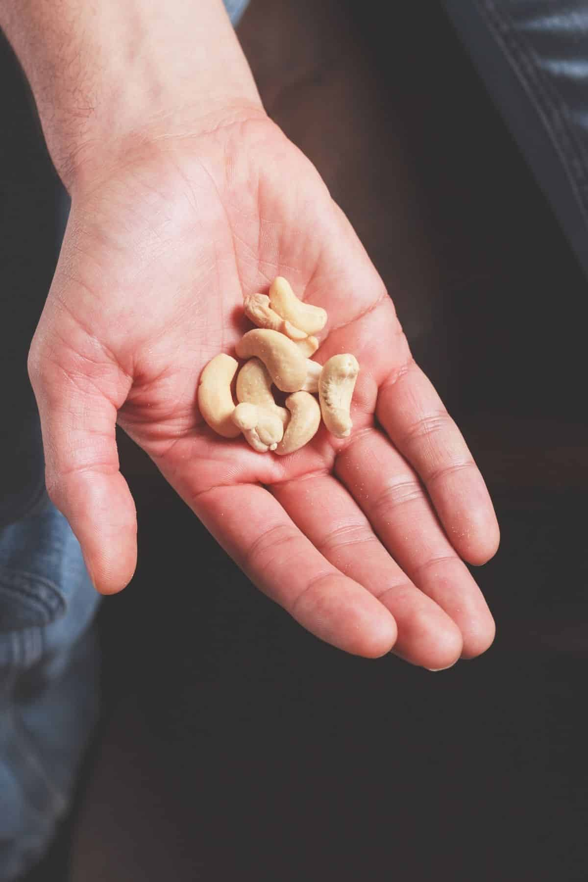 person holding a small handful of nuts