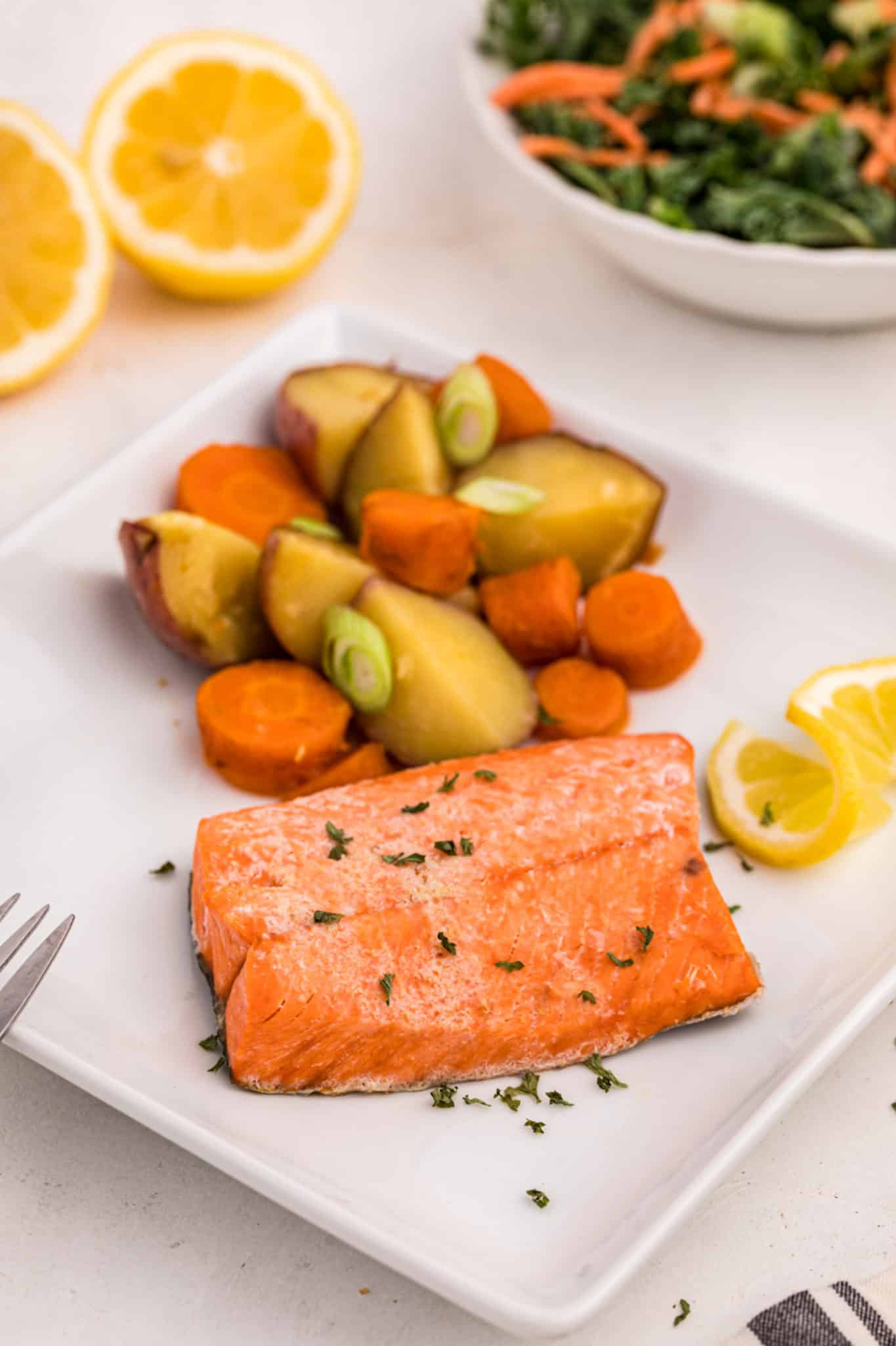 cooked salmon served with potatoes and carrots