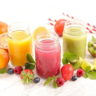 three colorful juices on a table