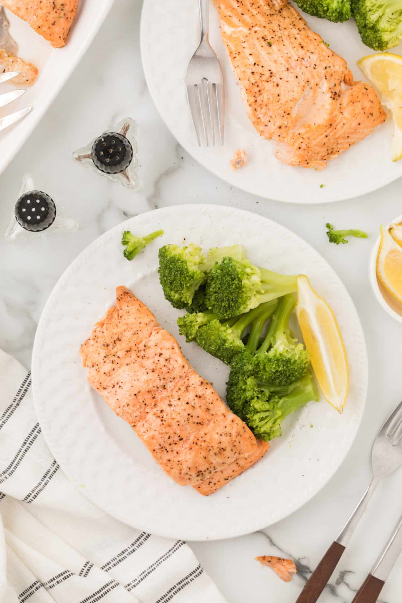 two plates of salmon dinner on a tabletop