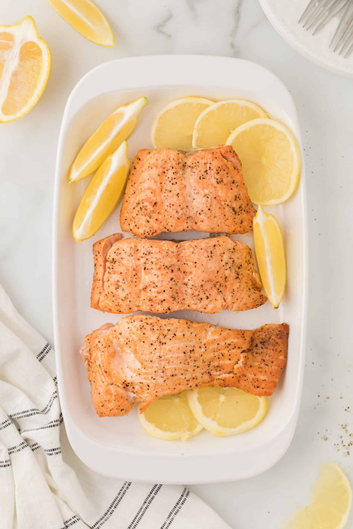 cooked salmon fillets on a serving dish with lemon slices