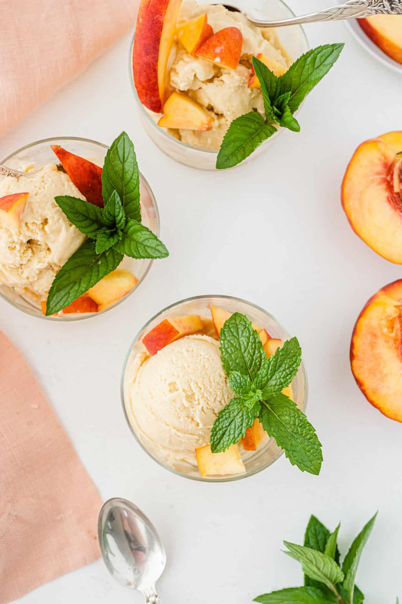 three bowls of peach ice cream on a table