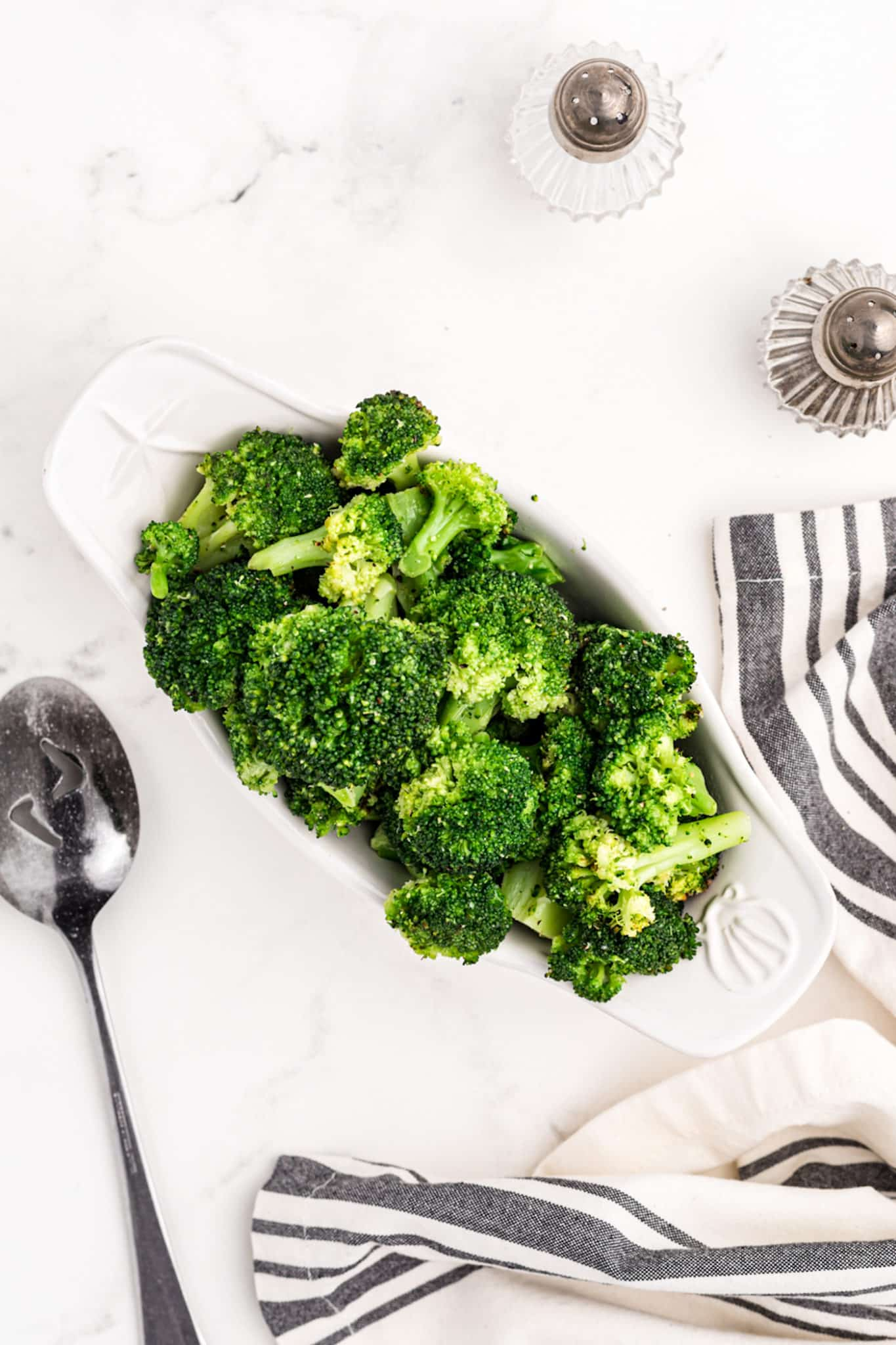 cooked broccoli served on a table with salt and pepper