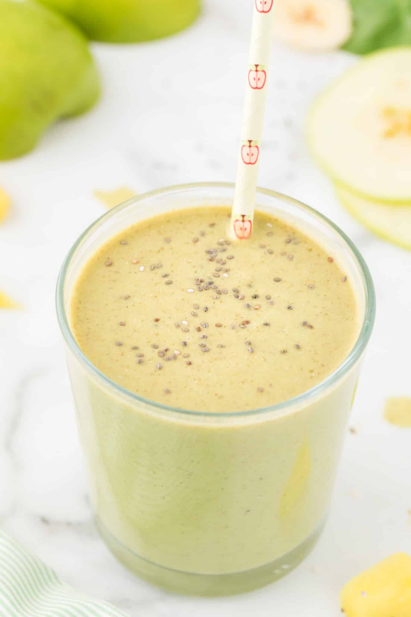 green apple smoothie served in glass and topped with chia seeds
