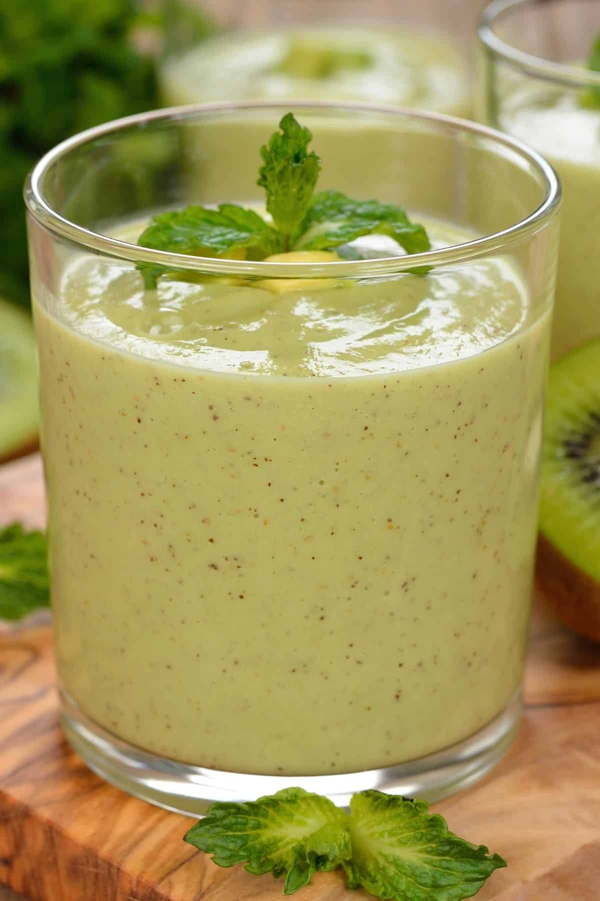 glass of green kiwi smoothie with fresh mint on top