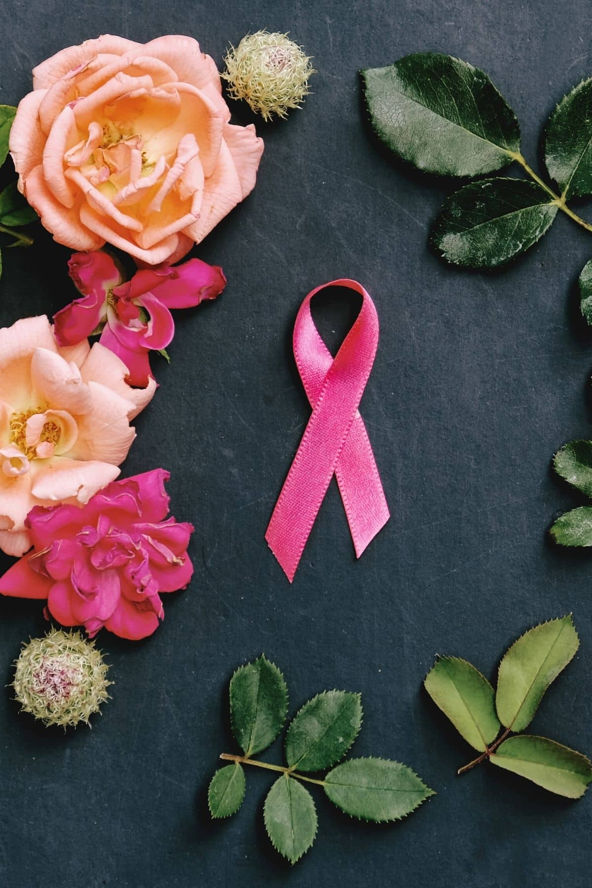 pink ribbon on a table with roses