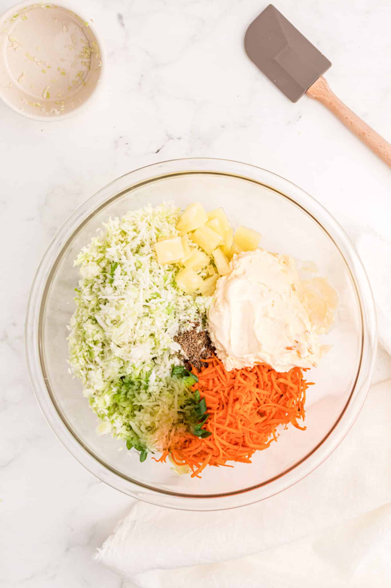 carrots, cabbage, pineapple, and mayonnaise in a bowl