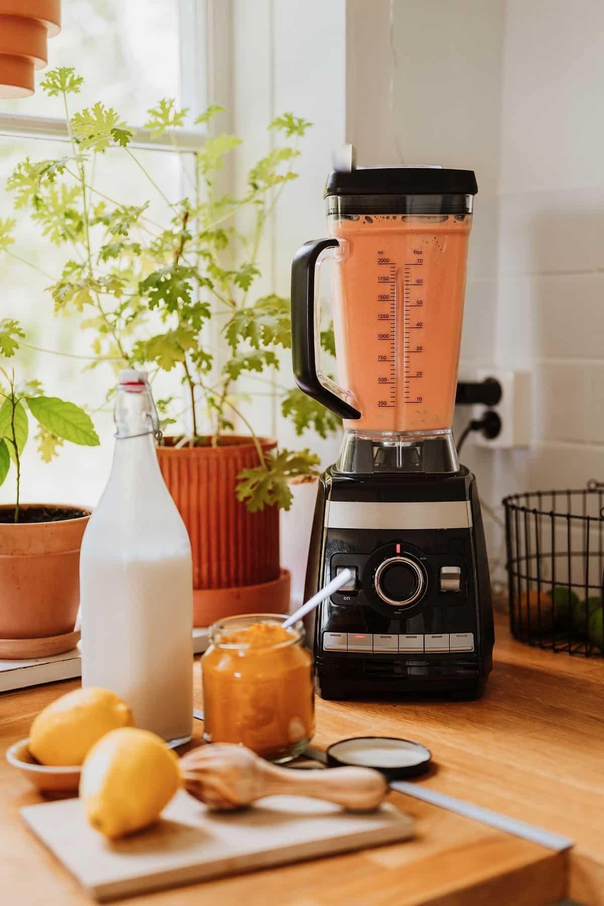 high powdered blender filled with orange smoothie