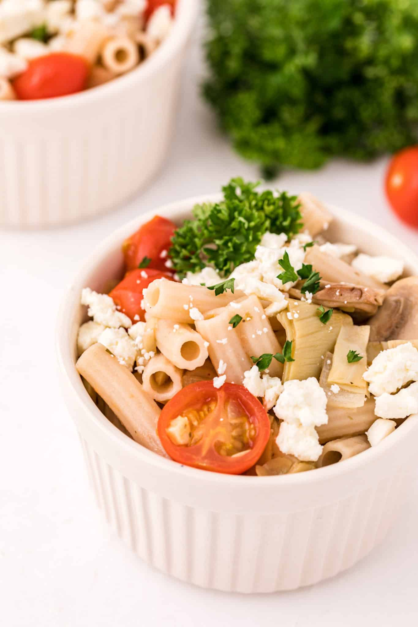 two bowls of vegetarian pasta with parsley on top