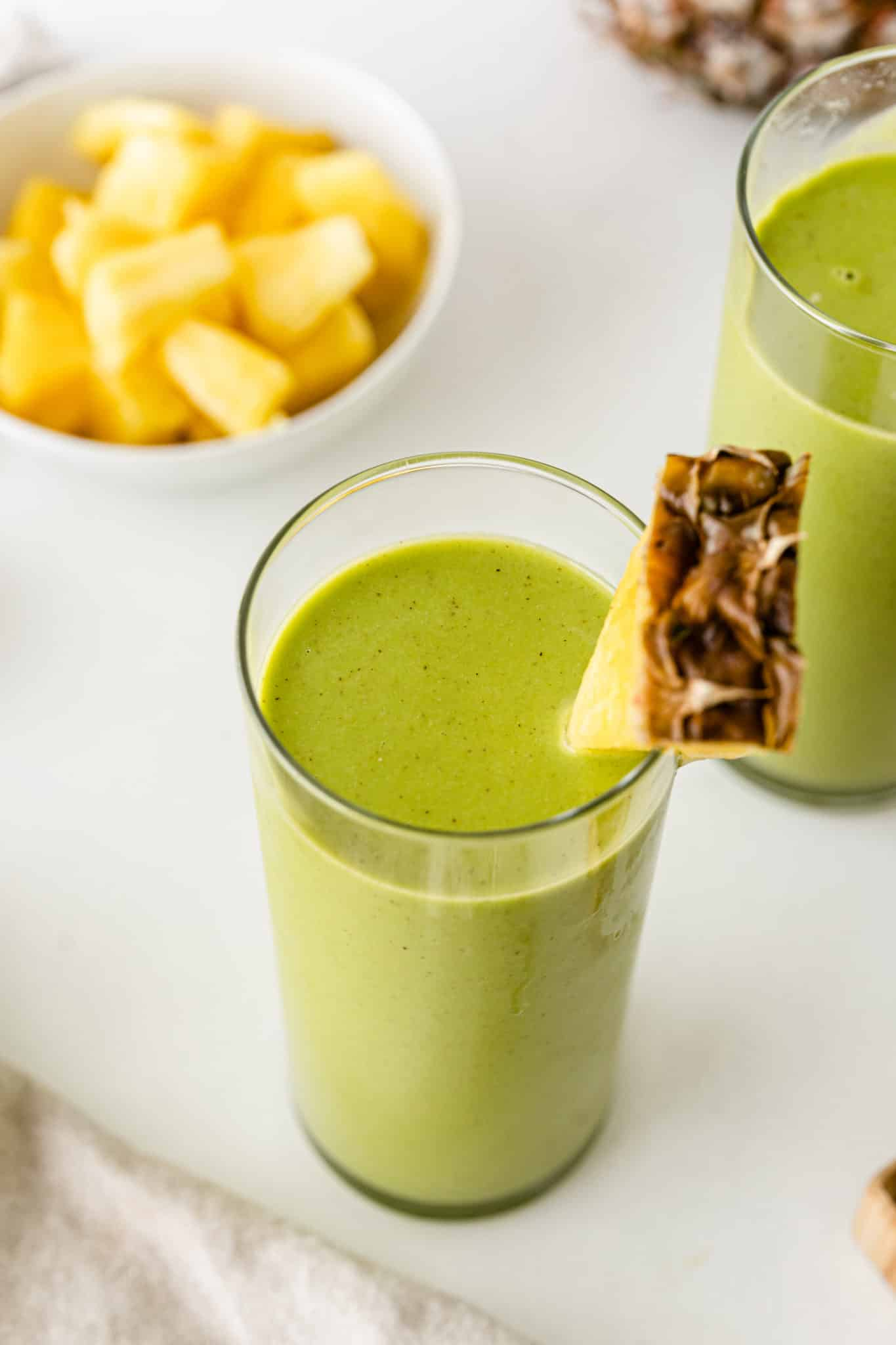 green smoothie served in a glass with a wedge of fresh pineapple