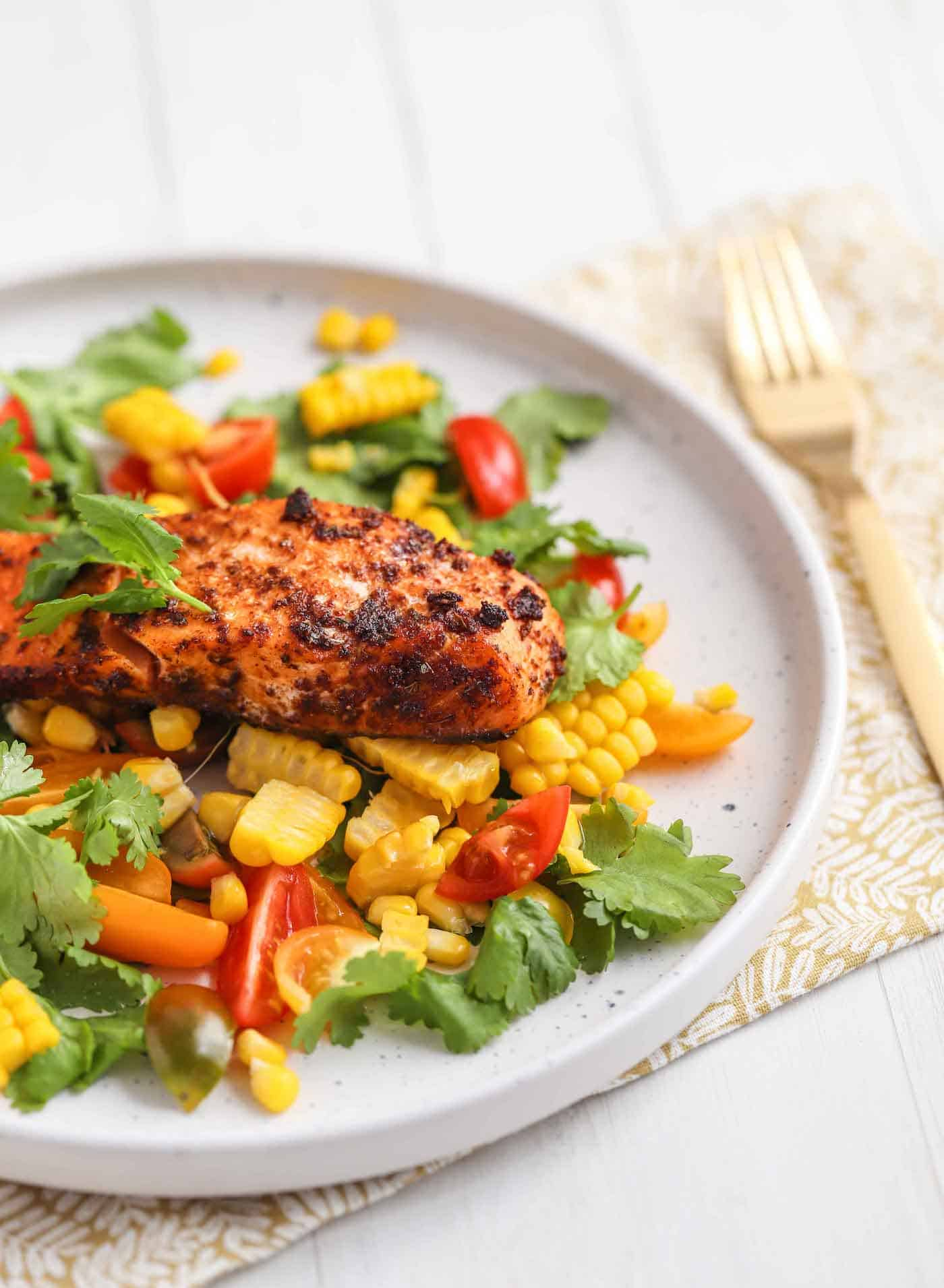 salmon served with salad and corn