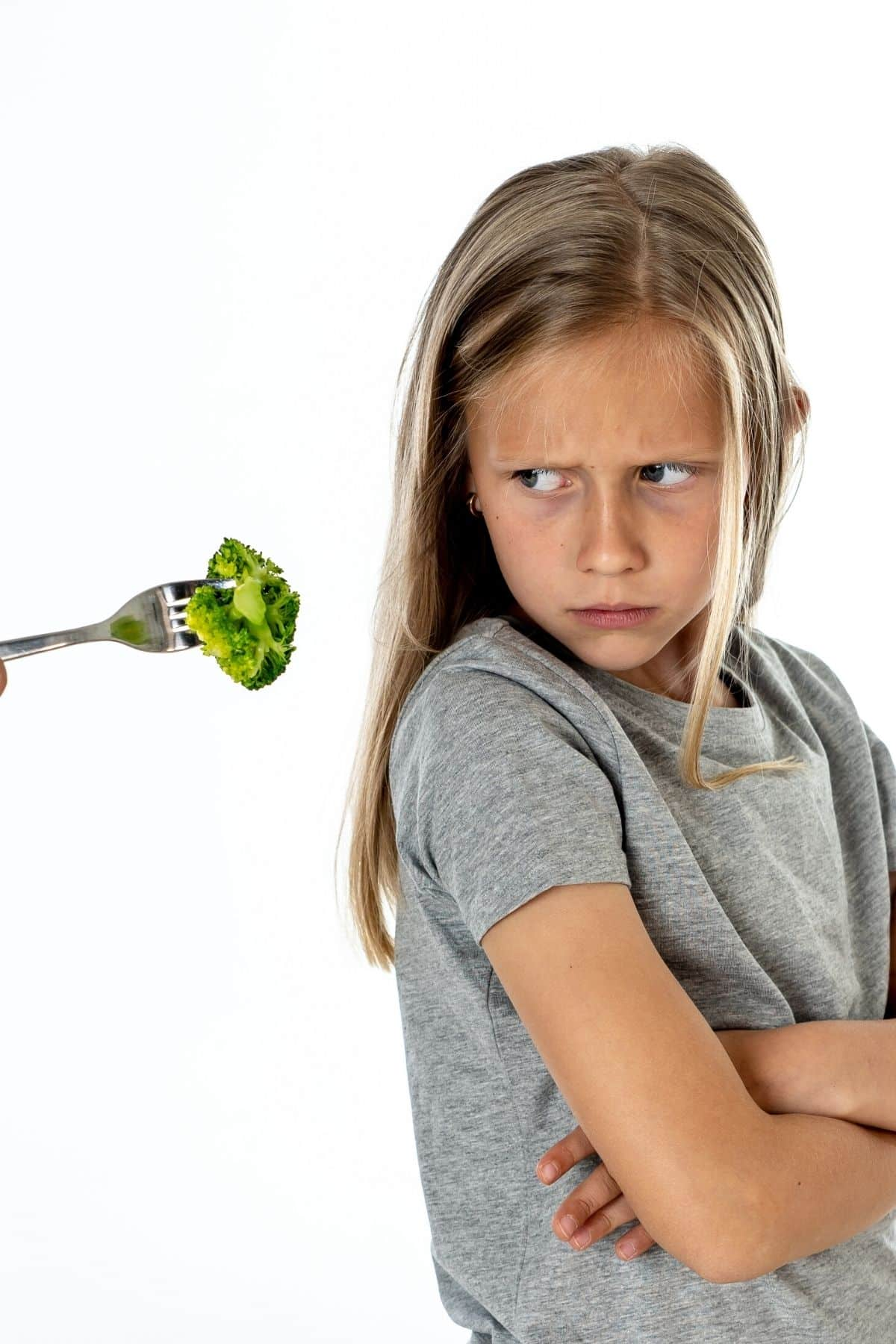 young girl refusing a bite of broccoli