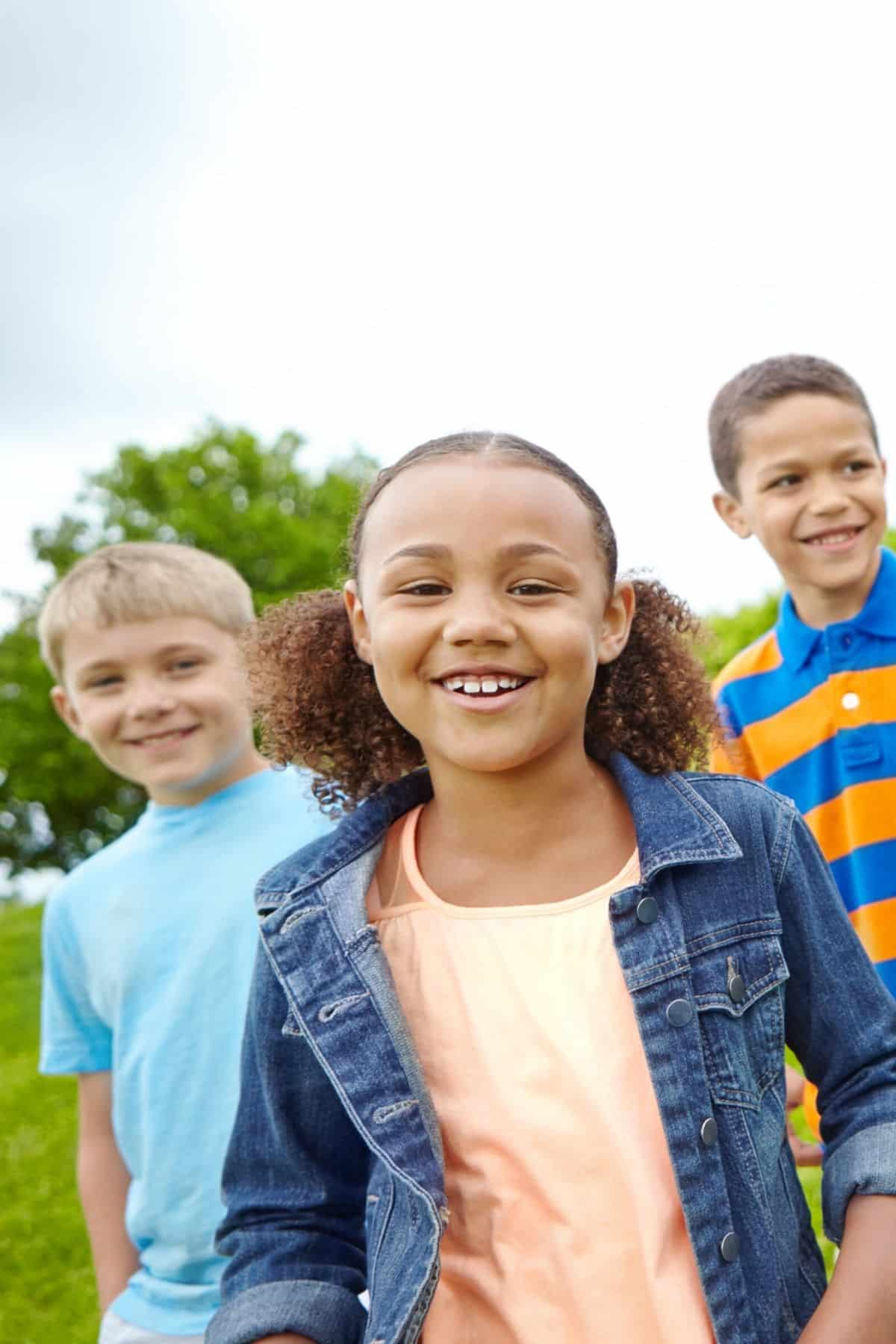 three smiling children at a park