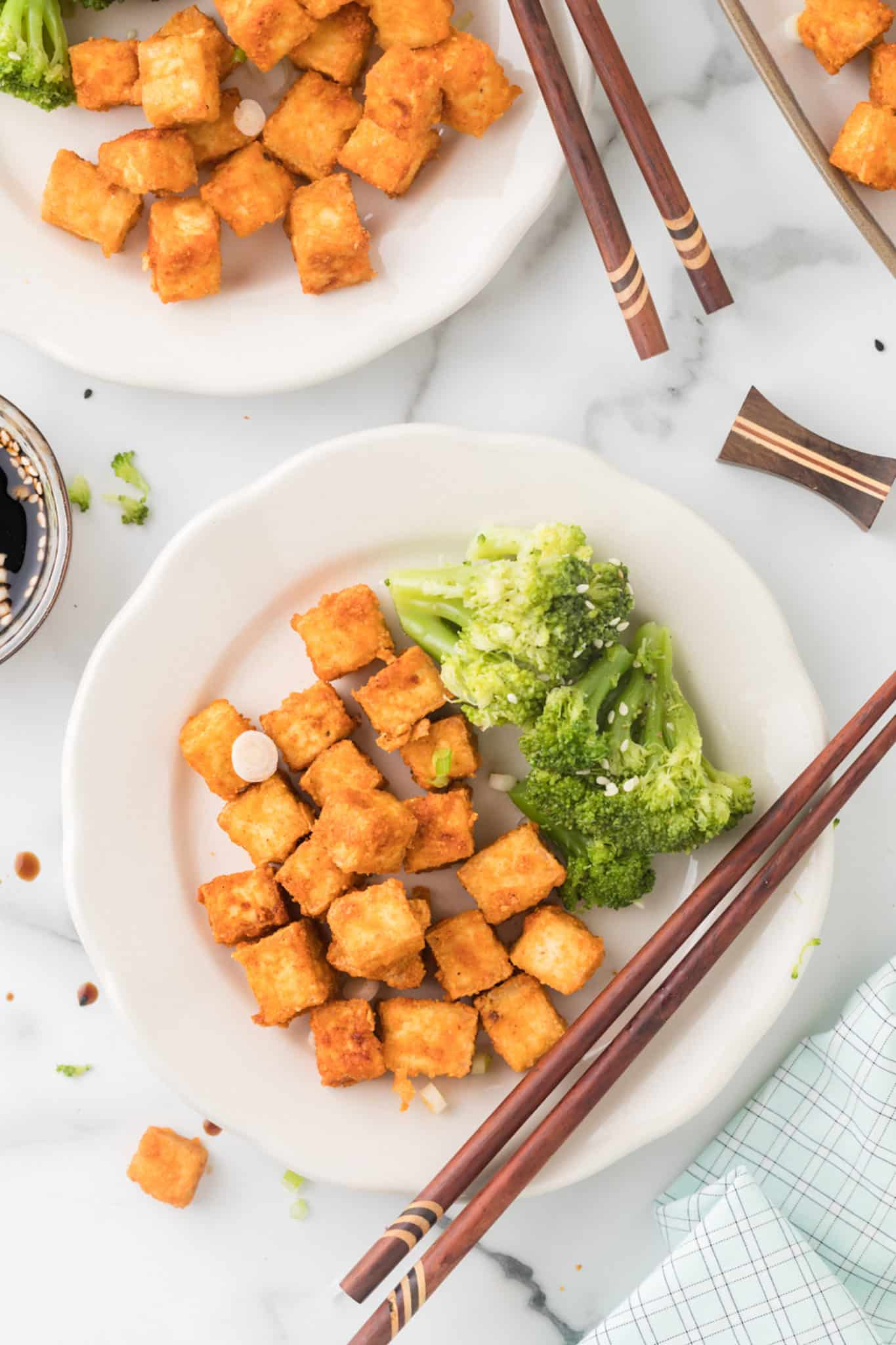 two plates of tofu served with broccoli