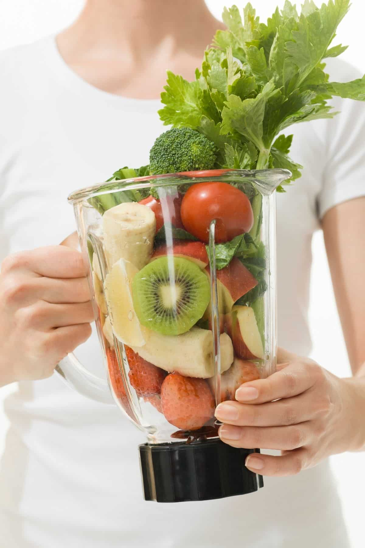 woman holding a blender with fruits and veggies in it