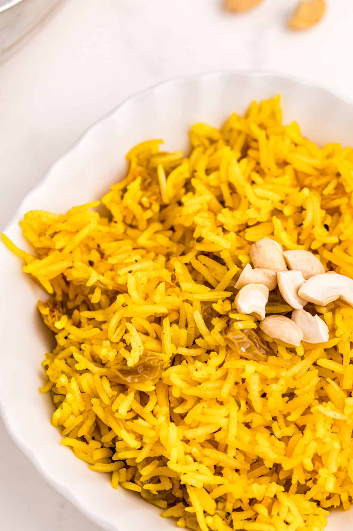 yellow rice served in a bowl with cashews on top