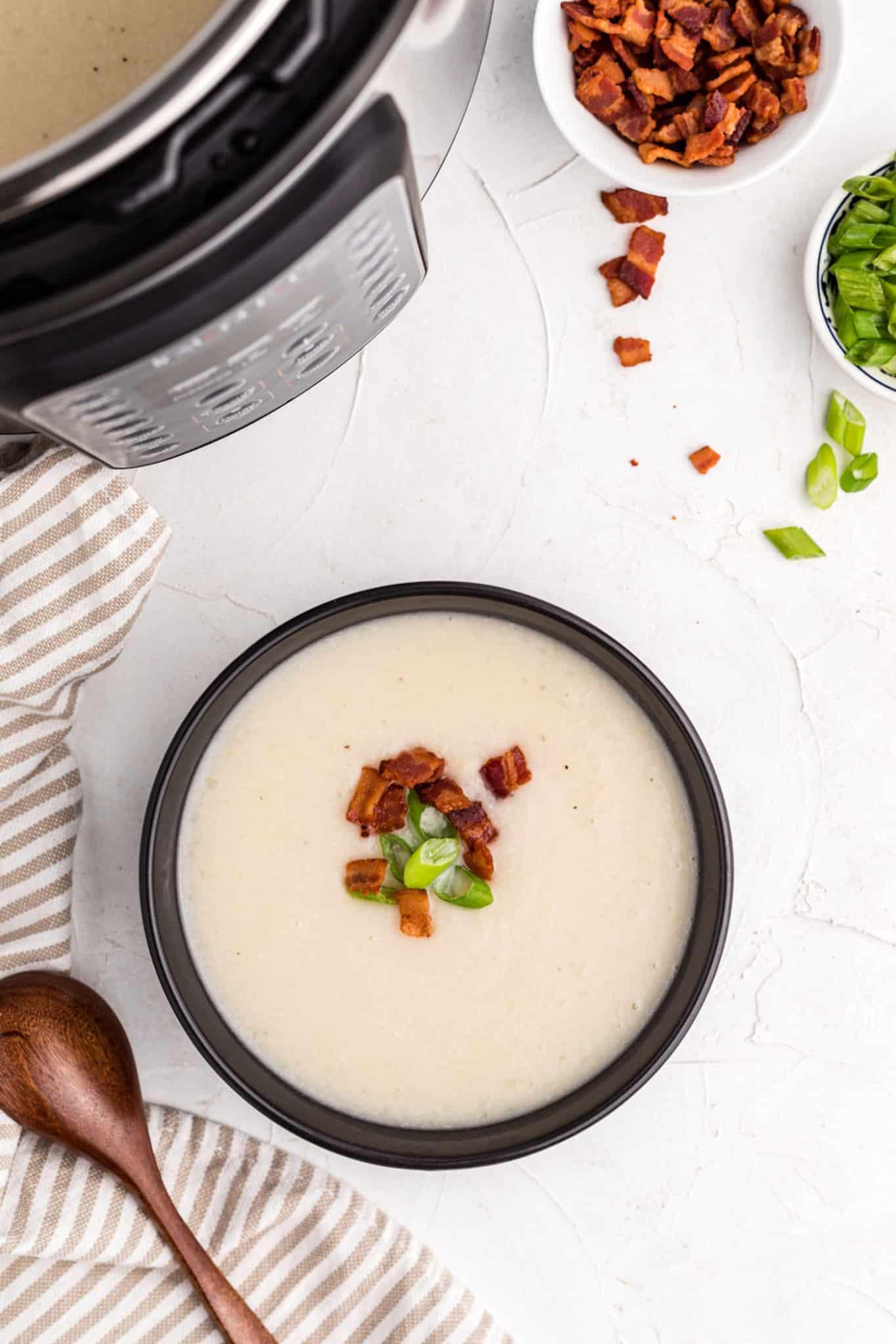 bowl of cauliflower soup next to an instant pot
