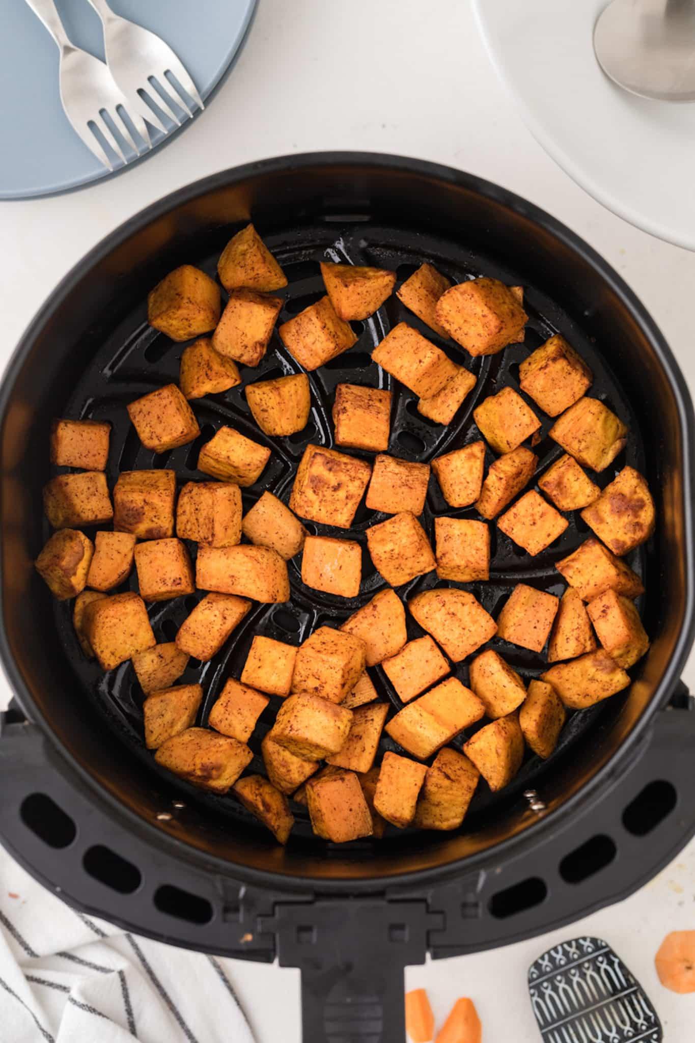 sweet potato cubes in an air fryer basket