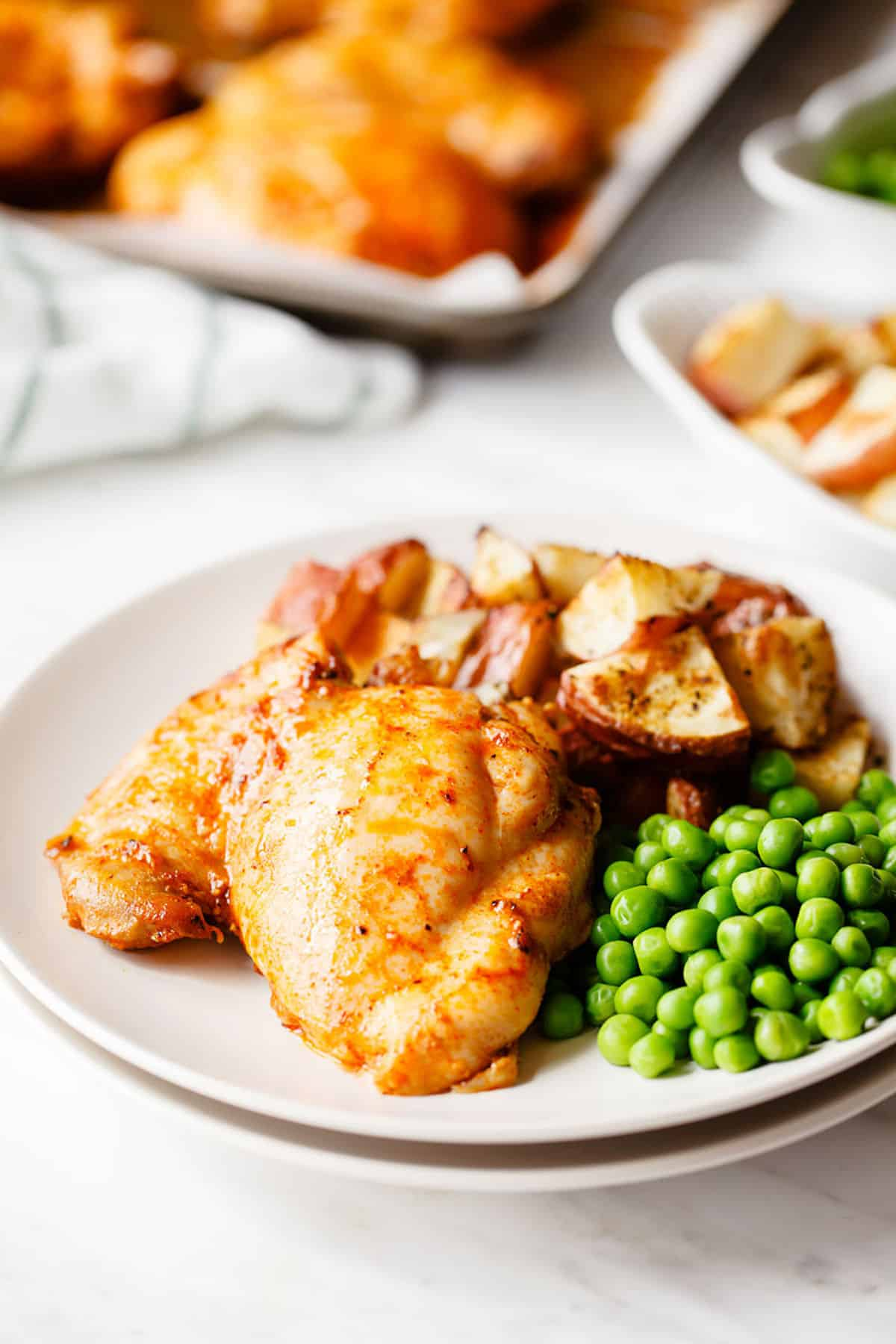 paprika chicken on a plate with peas and potatoes
