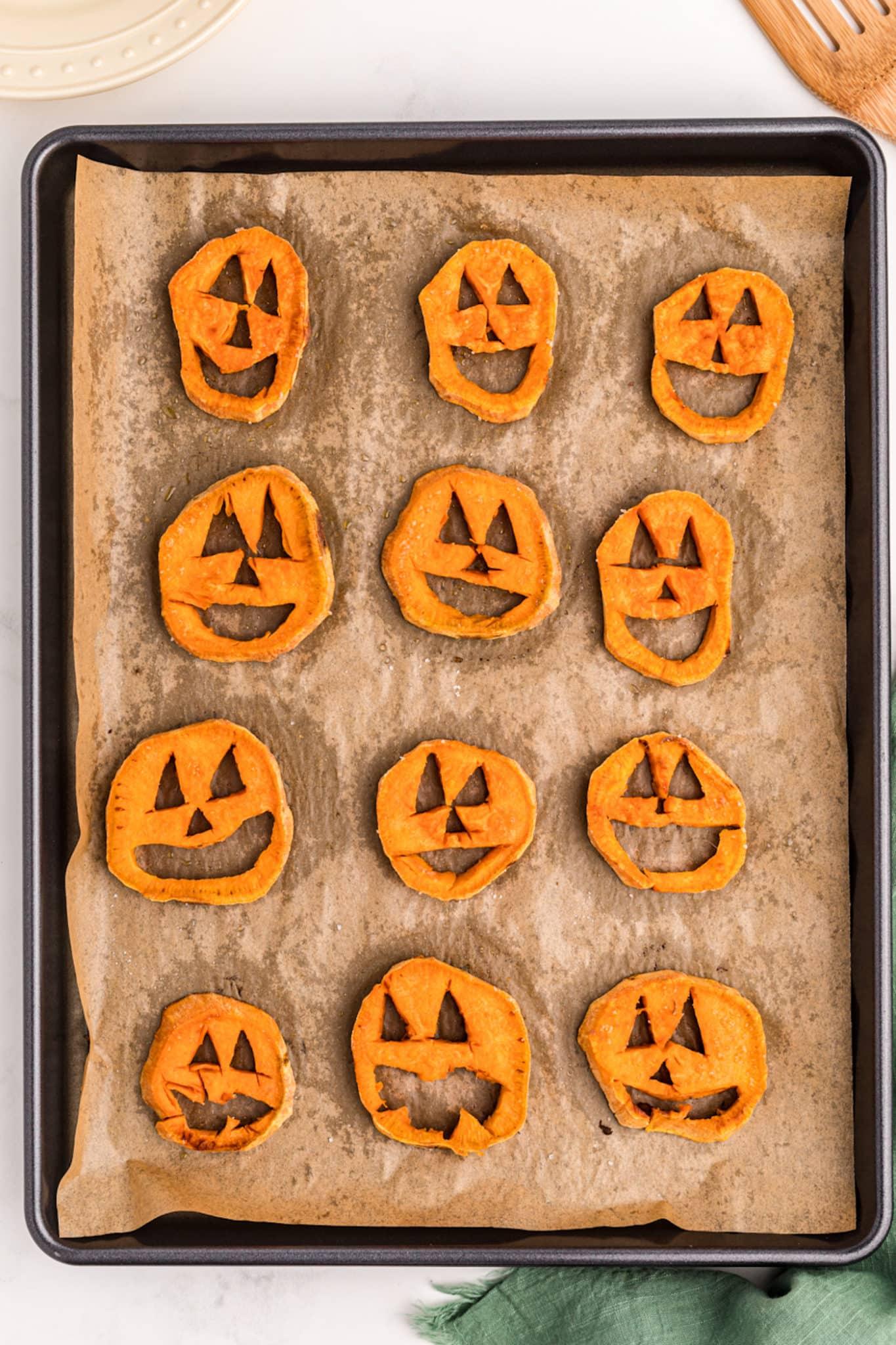 baked sweet potato jack o lanterns on a baking sheet