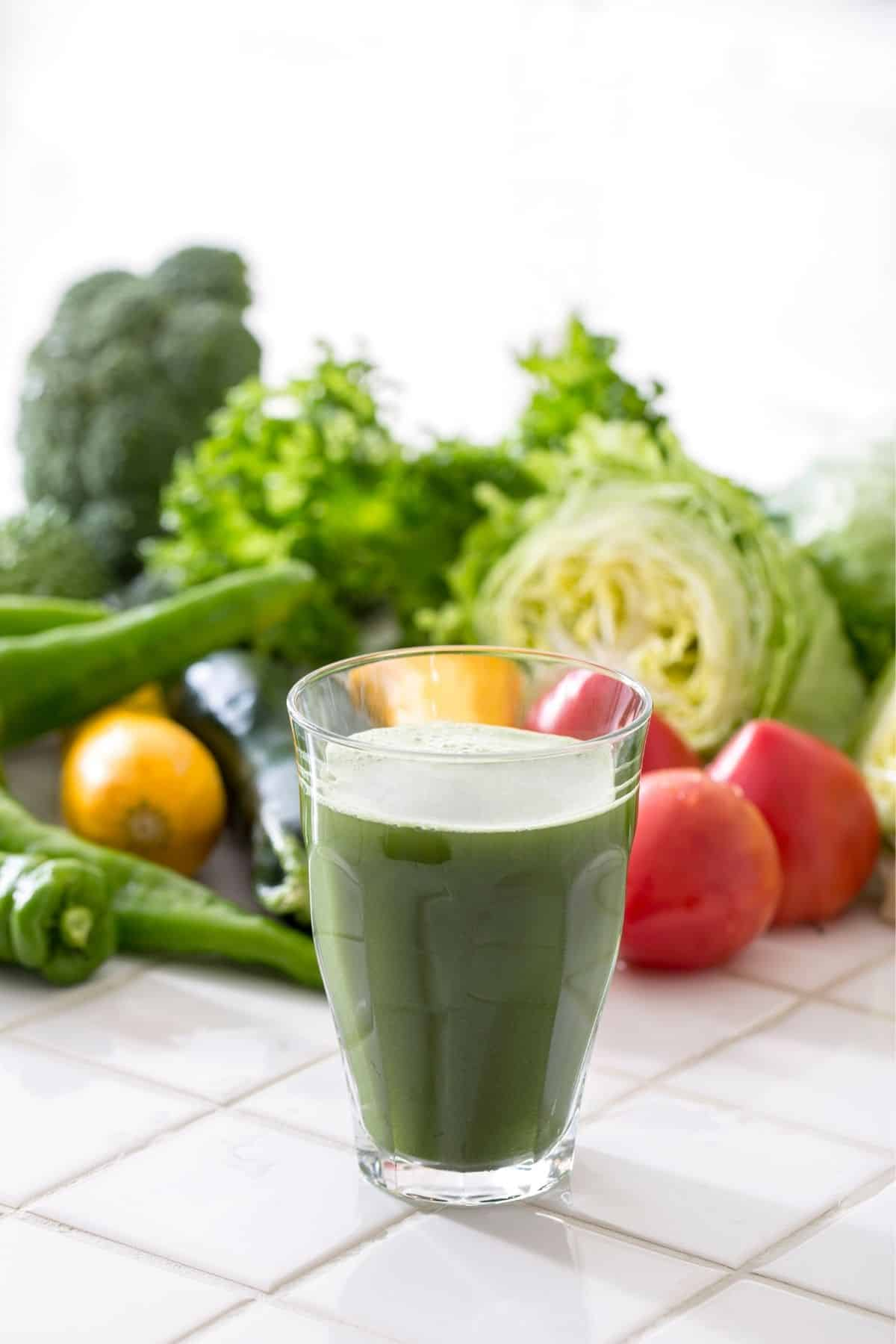 green juice on a table with fresh vegetables