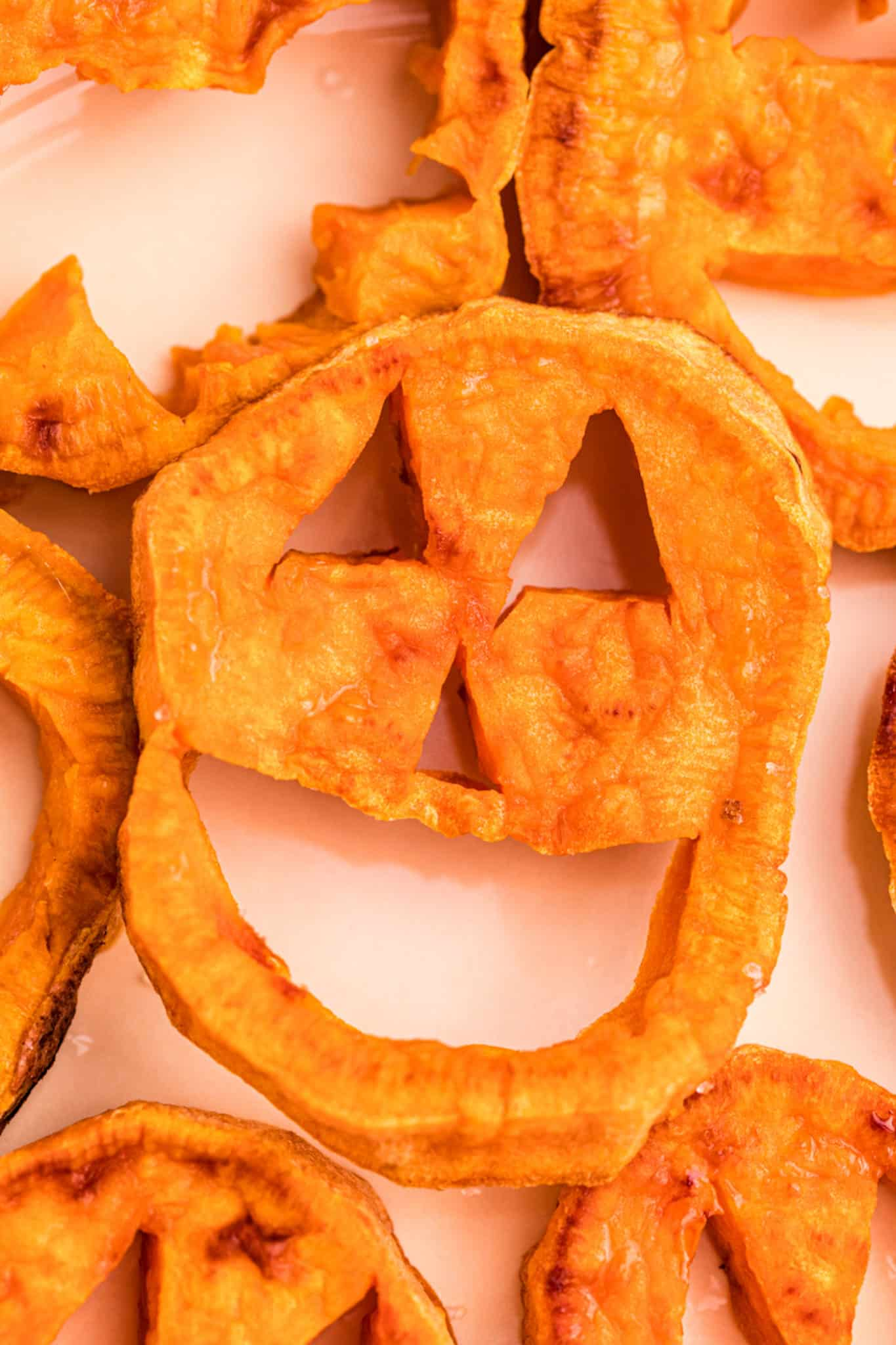 jack o lantern face cut into a slice of sweet potato